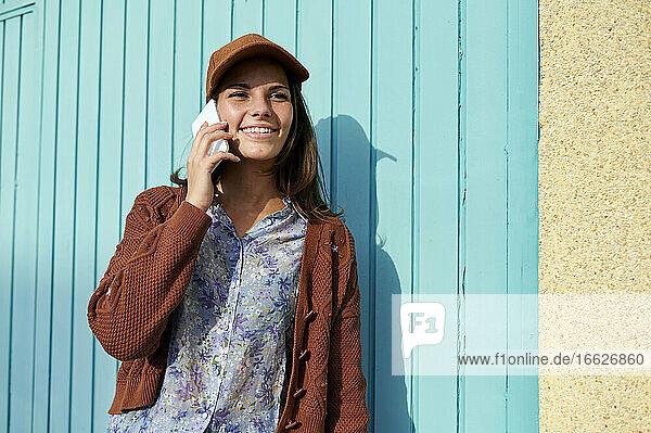 Junge Frau lächelt  während sie am Telefon gegen eine blaue Metalltür spricht Junge Frau lächelt, während sie am Telefon gegen eine blaue Metalltür spricht