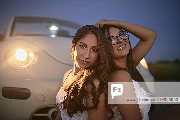 Freundinnen sitzen am Cabrio gegen den Himmel in der Abenddämmerung Freundinnen sitzen am Cabrio gegen den Himmel in der Abenddämmerung