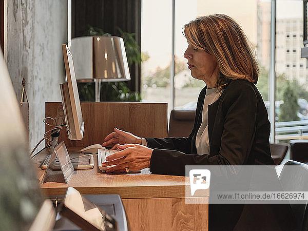 Ältere Frau arbeitet am Computer  während sie im Hotel sitzt Ältere Frau arbeitet am Computer, während sie im Hotel sitzt