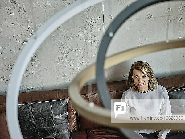 Senior woman looking away while sitting in hotel lobby