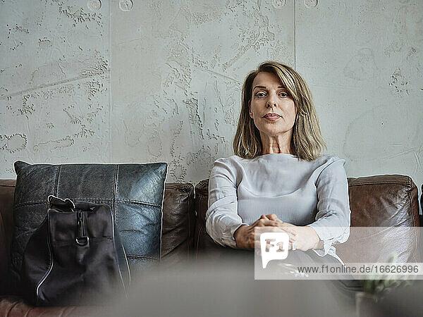Senior woman sitting on sofa in hotel lobby