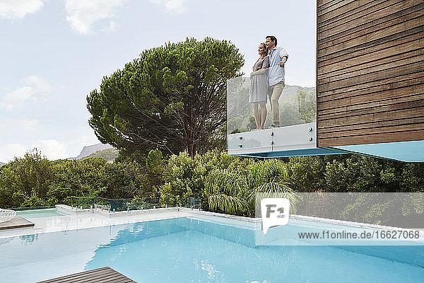 Niedriger Blickwinkel auf ein Paar  das auf einem Balkon steht Niedriger Blickwinkel auf ein Paar, das auf einem Balkon steht
