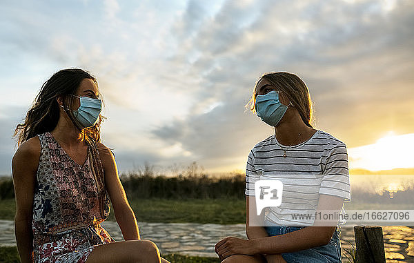 Women in protective face masks maintaining social distance while sitting against sky during sunset