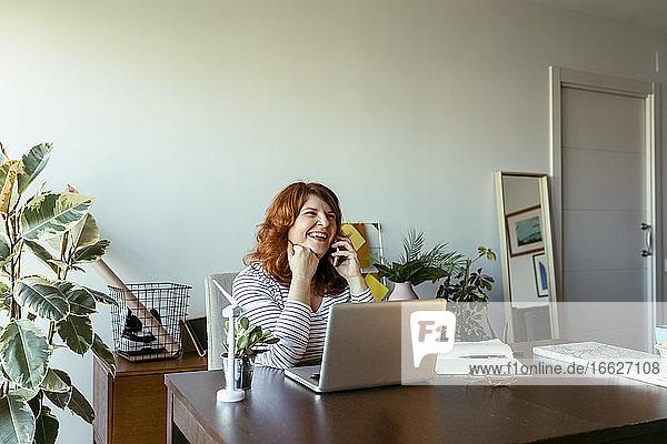 Frau lächelt  während sie zu Hause telefoniert Frau lächelt, während sie zu Hause telefoniert