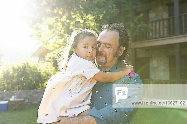 Vater hält Tochter im Hinterhof stehend Vater hält Tochter im Hinterhof stehend
