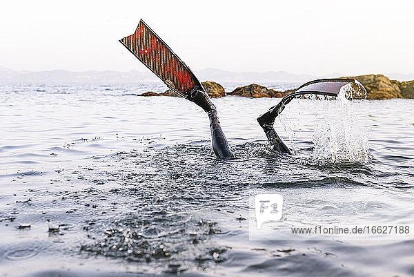 Beine eines Mannes mit Flossen tauchen im Meer gegen klaren Himmel Beine eines Mannes mit Flossen tauchen im Meer gegen klaren Himmel