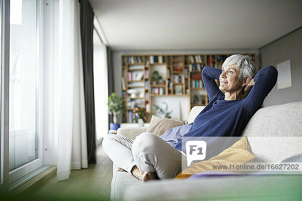 Senior woman with hands behind head with cross legged sitting on sofa at home