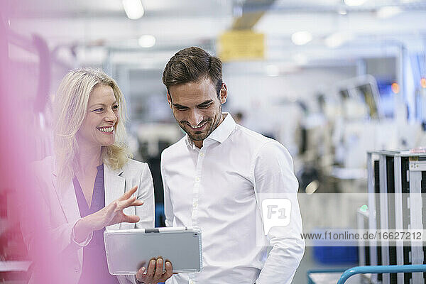 Smiling businesswoman discussing with young male colleague in illuminated factory