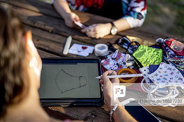 Friends designing face mask on digital tablet while sitting outdoors