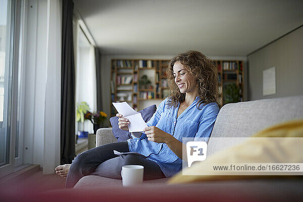 Woman reading paper while sitting on sofa at home