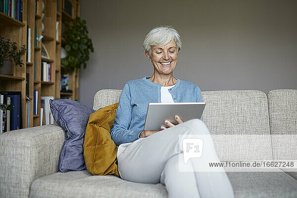 Smiling senior woman using digital tablet while sitting at home