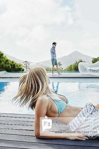 Junge Frau sieht reifen Mann an  der in der Nähe des Swimmingpools mit einem Smartphone spricht Junge Frau sieht reifen Mann an, der in der Nähe des Swimmingpools mit einem Smartphone spricht