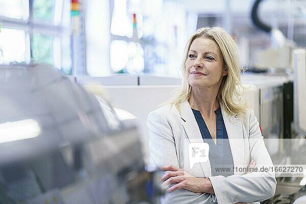 Thoughtful blond female professional standing with arms crossed in illuminated factory