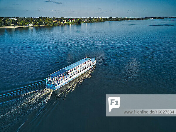 Ship with wake on blue Volga River