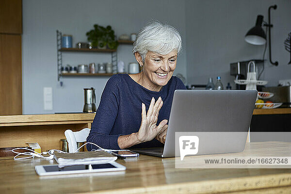 Active senior woman doing high five on video call while using laptop at home