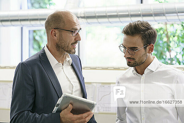 Businessman discussing with male technician over digital tablet at factory