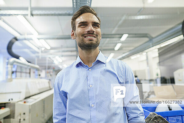 Smiling young male engineer looking away while standing at illuminated factory