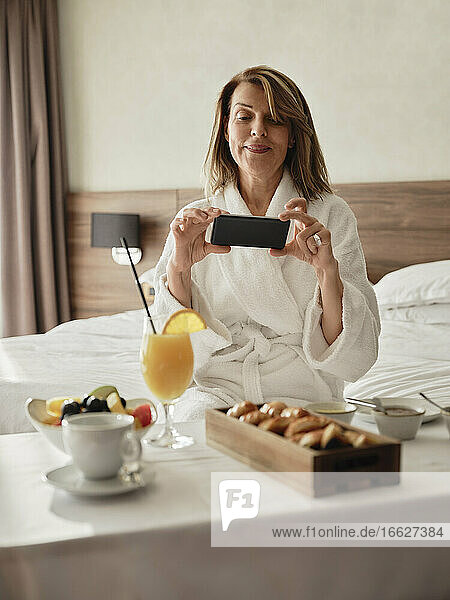 Smiling blond senior woman photographing breakfast through smart phone while sitting on bed in hotel room