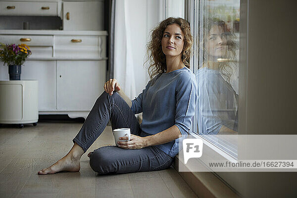Woman looking away while sitting on floor at home