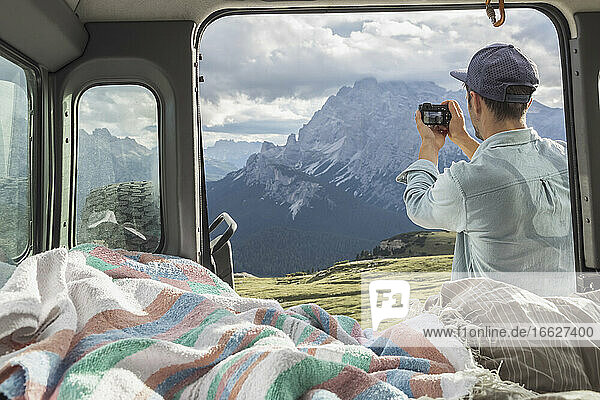 Man photographing scenic mountain ranges while standing by campervan. Sesto Dolomites  Dolomites  Alto Adige  Italy