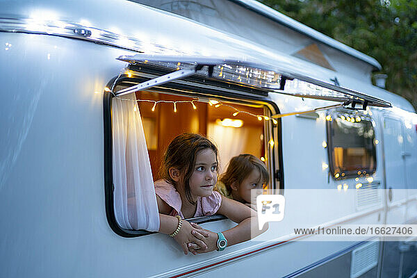 Cute sisters looking through window of illuminated motor home at dusk