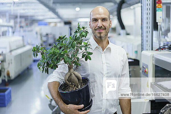 Smiling confident businessman holding potted plant while standing at factory