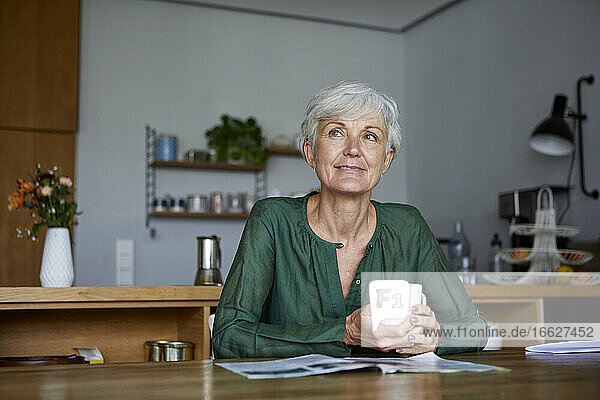 Thoughtful senior woman sitting with coffee cup at home