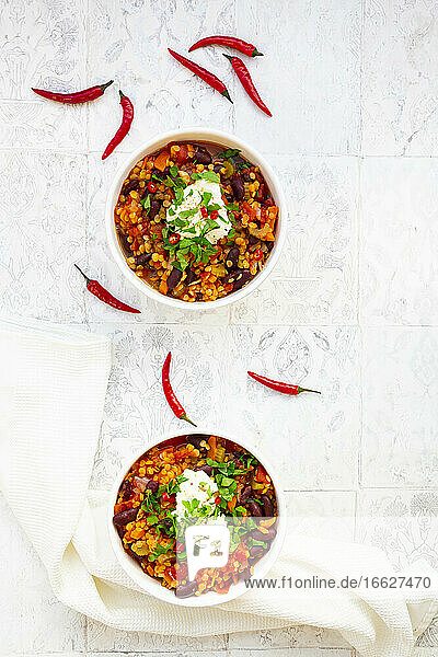 Two bowls of vegetarian stew with red lentils  chili peppers  celery  kidney beans  tomatoes  carrots and sour cream