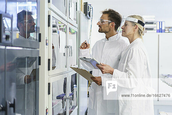 Young male technician analyzing while standing by female colleague at illuminated laboratory