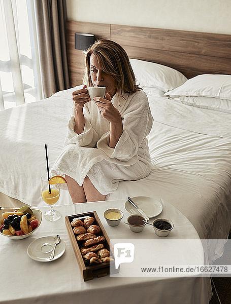 Blonde ältere Frau trinkt Kaffee und genießt das Frühstück in einem luxuriösen Hotelzimmer Blonde ältere Frau trinkt Kaffee und genießt das Frühstück in einem luxuriösen Hotelzimmer