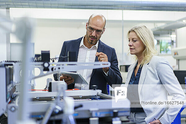 Confident businessman and businesswoman discussing while looking at machinery in factory
