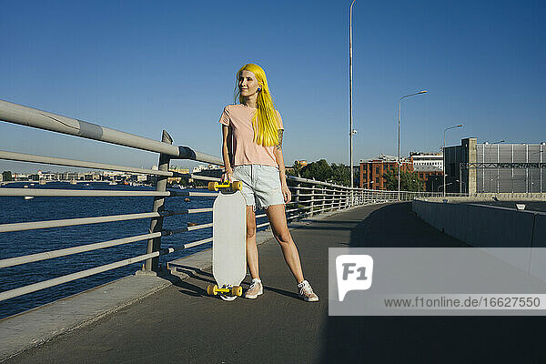 Young woman standing on bridge looking away during sunny day