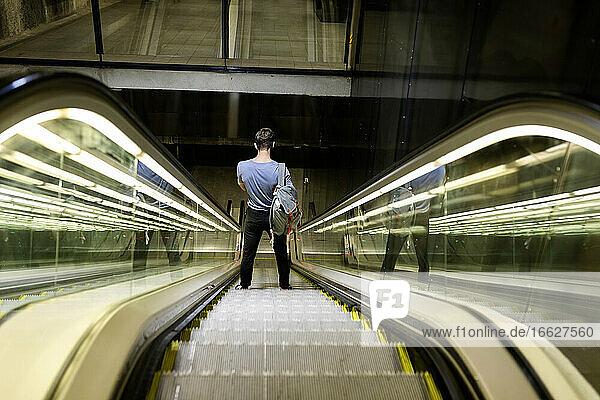 Junger Mann mit Rucksack steht auf beleuchteter Rolltreppe in der U-Bahn Junger Mann mit Rucksack steht auf beleuchteter Rolltreppe in der U-Bahn