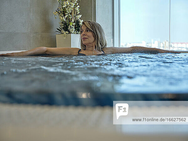 Senior woman in swimming pool at health spa
