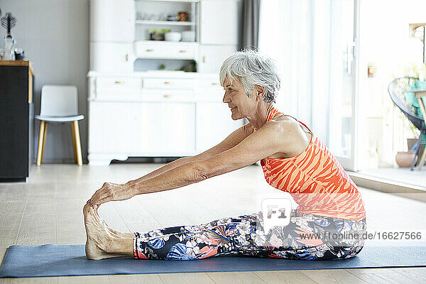 Fit senior woman stretching leg and back while exercising at home