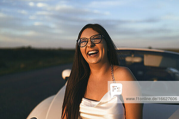 Cheerful woman laughing while standing against car