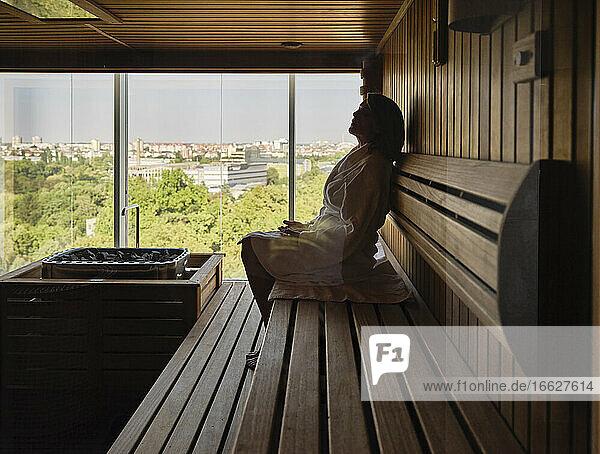 Senior woman sitting on wooden sauna at health spa