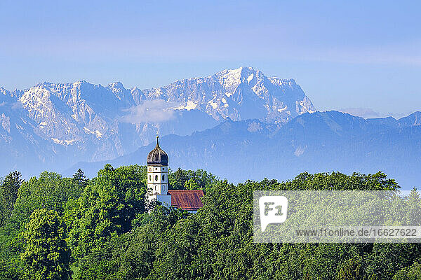Germany  Bavaria  Holzhausen  Saint Johann Baptist church surrounded by green forest in summer with Zugspitze in distant background