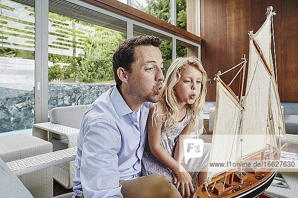 Vater und Tochter blasen Spielzeugboot  während sie zu Hause sitzen Vater und Tochter blasen Spielzeugboot, während sie zu Hause sitzen