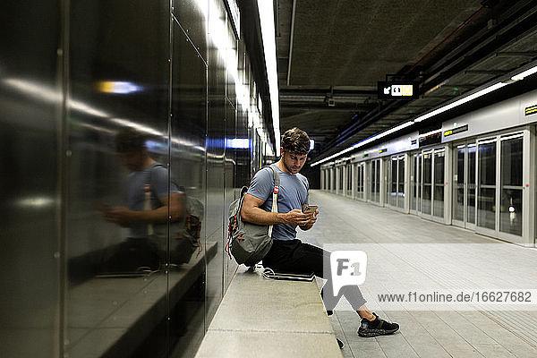 Junger Mann  der sein Smartphone benutzt  während er auf einer Bank an der Wand in einer beleuchteten U-Bahn sitzt Junger Mann, der sein Smartphone benutzt, während er auf einer Bank an der Wand in einer beleuchteten U-Bahn sitzt
