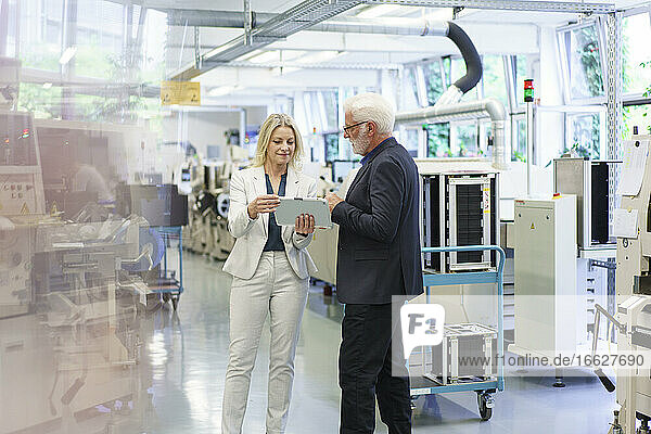 Confident businesswoman discussing over digital tablet with senior businessman in factory