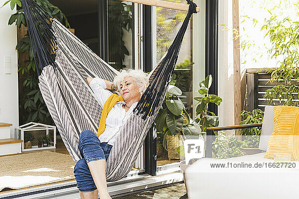 Mature woman with hands behind head sitting on hammock at home