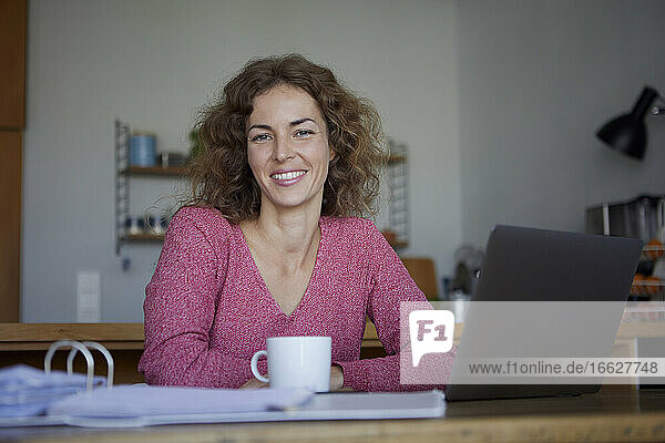 Smiling woman using laptop while working at home