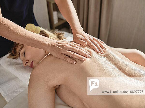 Ältere Frau gibt Rückenmassage an ältere Frau im Wellnessbereich Ältere Frau gibt Rückenmassage an ältere Frau im Wellnessbereich