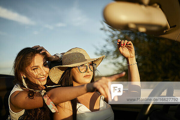 Smiling young friends pointing while sitting in convertible car