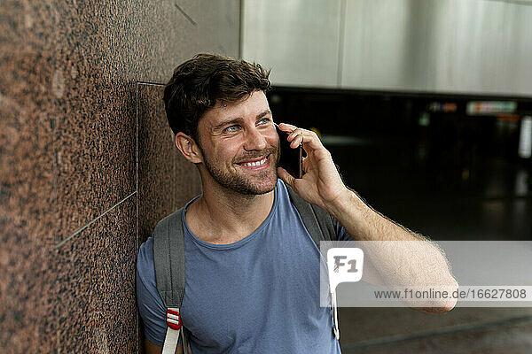Glücklicher Mann  der mit seinem Handy spricht  während er wegschaut und sich an eine braune Kachelwand in einer U-Bahn-Station lehnt Glücklicher Mann, der mit seinem Handy spricht, während er wegschaut und sich an eine braune Kachelwand in einer U-Bahn-Station lehnt
