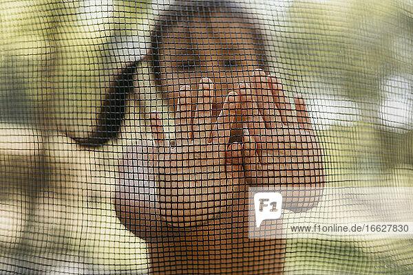Mädchen schiebt das Netz mit der Hand  während sie im Hinterhof steht Mädchen schiebt das Netz mit der Hand, während sie im Hinterhof steht
