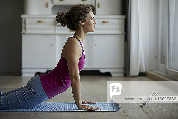 Woman using digital tablet while doing yoga at home