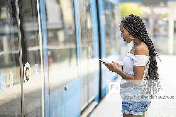 Young woman using phone while standing by tram in city