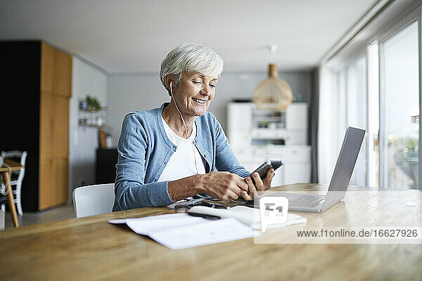 Active senior female listening to music while sitting at home